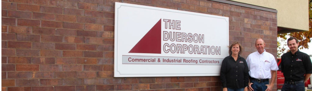 family members of the duer family stand in front the of the duerson corporation sign